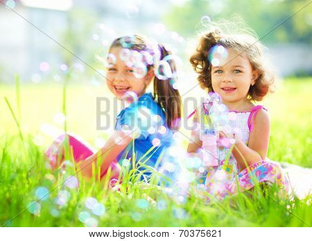 Two little girls are blowing soap bubbles, outdoor shoot