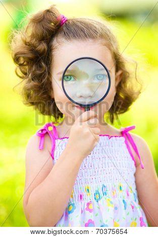Little girl is looking through magnifier, outdoor shoot