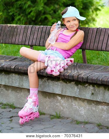 Little girl is wearing roller-blades in city park and drinking mineral water