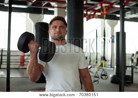 Portrait of strong man exercising with dumbbells