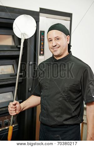 portrait of chef baker in uniform with pizza shovel at restaurant kitchen
