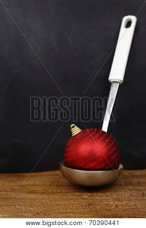 Christmas ball in a serving spoon and copy space on black background