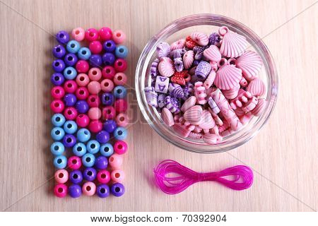 Multicoloured beads and lace stacked neatly on the table