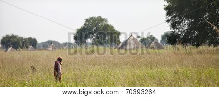LILIIR, SOUTH SUDAN-DECEMBER 4 2010: an unidentified tribesman walks past his village of Liliir in South Sudan