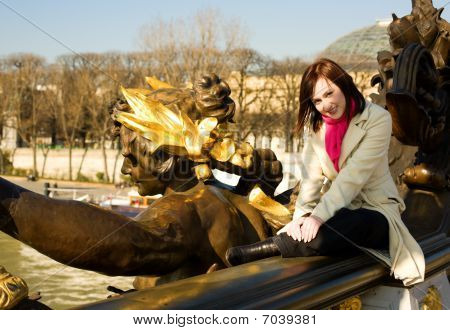 Beautiful Woman Sitting On The Balustrade Of The Pont Alexandre Iii In Paris, France