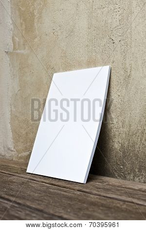 Booklet With White Cover At Wooden Floor And Old Wall