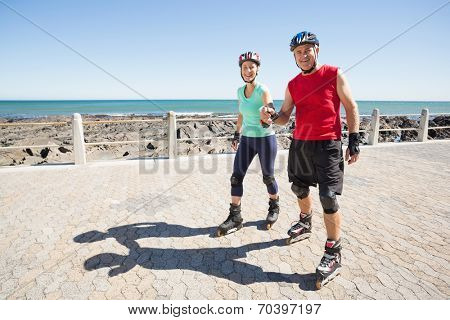 Fit mature couple rollerblading on the pier on a sunny day
