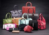 image of primite  - Set of beautiful leather handbags on black background - JPG
