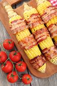 picture of corn cob close-up  - Grilled bacon wrapped corn on table - JPG