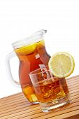 stock photo of iced-tea  - Ice tea pitcher and glasss with lemon and icecubes on wooden background - JPG