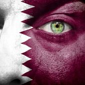 stock photo of qatar  - Flag painted on face with green eye to show Qatar support - JPG