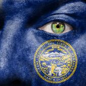 foto of nebraska  - Flag painted on face with green eye to show Nebraska support - JPG