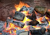 picture of fiery  - Glowing coals in a wood fire with fiery orange flames in a brick hearth or fireplace with a wrought iron backplate - JPG