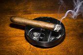 stock photo of cigar  - A burning cigar in a classic black ashtray streaming smoking in a dark - JPG