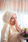 stock photo of shy girl  - Shy muslim girl smiling with flowers in her hands - JPG