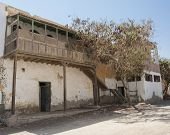stock photo of derelict  - Old derelict abandoned building with wooden balcony in an african egyptian town - JPG