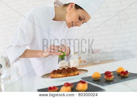 Pastry-cook shreding lemon zest over cake bites
