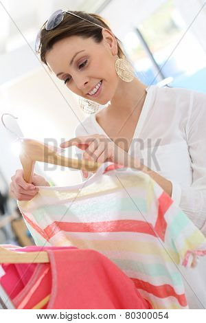 Beautiful woman in clothing store looking at price tag