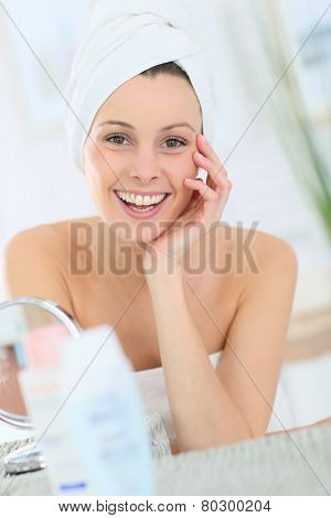 Cheerful woman in bathroom with towel over hair