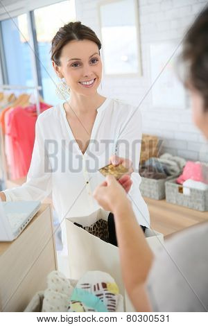 Customer in clothing store giving credit card to seller