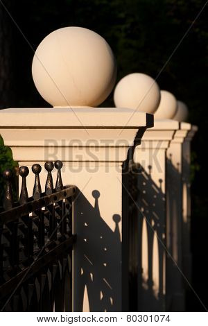 Decorative Balls On The Fence Near The House