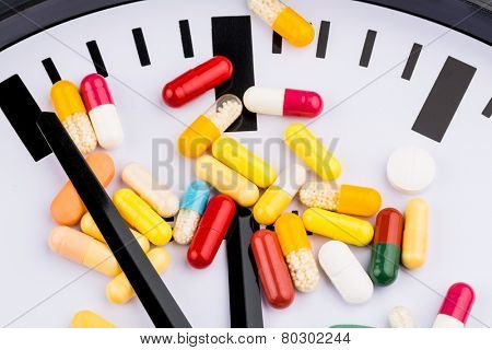 colorful capsules on a clock, symbolic photo for health care, health care reform, reform deadlock