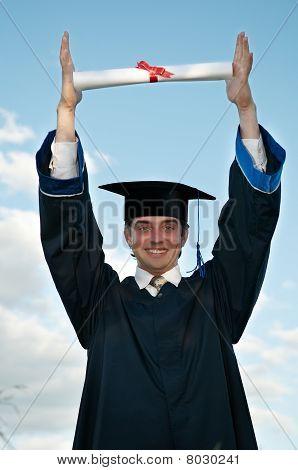 Graduado con Diploma en las manos sobre la cabeza