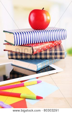 Pile of books with tablet on wooden table and light background