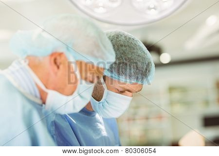 Older surgeon teaching new surgeon how to operate at the university