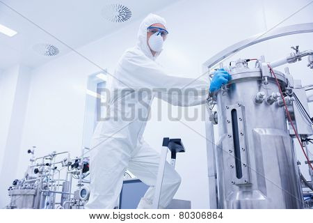 Scientist standing on ladder looking at the camera in the factory