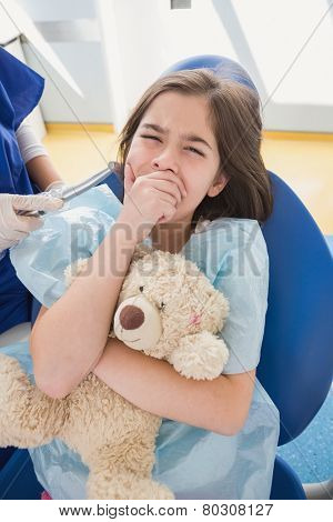 Scared patient covering mouth and holding teddy bear in dental clinic