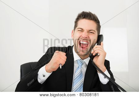 Businessman Screaming While Using Landline Phone In Office
