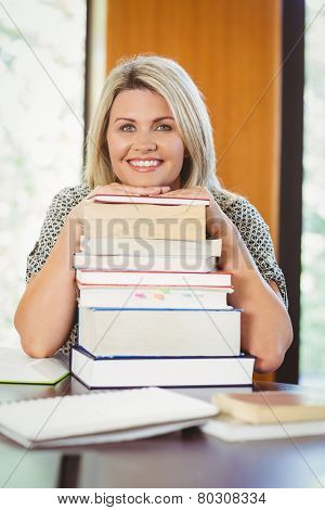 Smiling mature student with stack of books in library