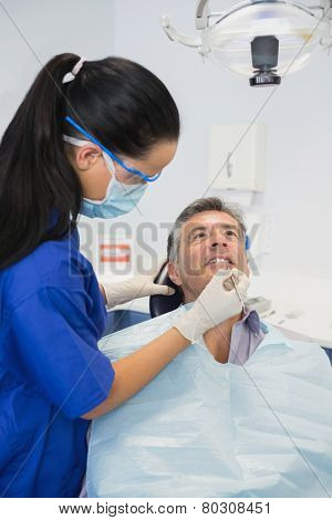 Dentist wearing surgical mask and safety glasses examining a patient