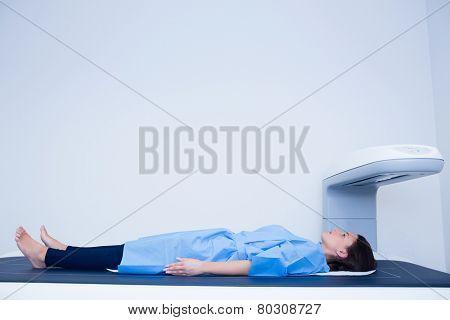 Sick woman lying on a x-ray machine in hospital
