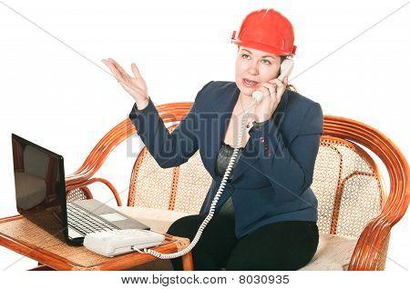 Das Mädchen in eine rote Helm mit dem Laptop sitzt auf einem Tisch und -Anrufe. isoliert auf weiß bac