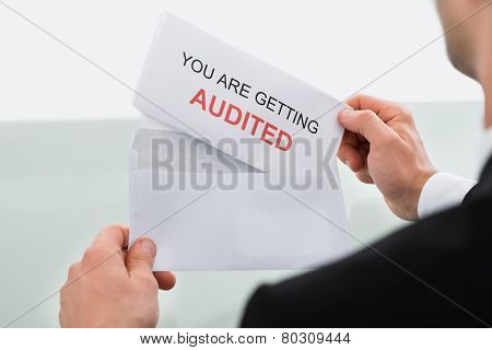 Businessman Opening Audit Letter In Office