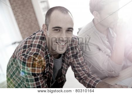 Smiling guy in shared apartment with roommates