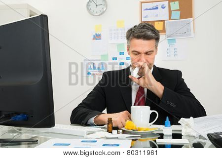 Businessman Spraying Nasal Spray In His Nose