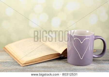 Cup of tea and book on table, on light background