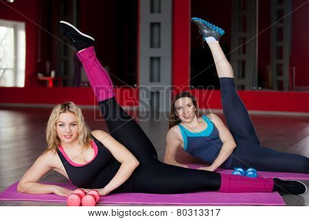 Two Smiling Girls Exercise On Mats In Fitness Center