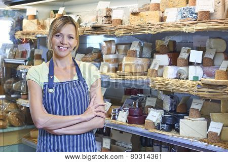 Owner Of Delicatessen Standing Next To Cheese Display