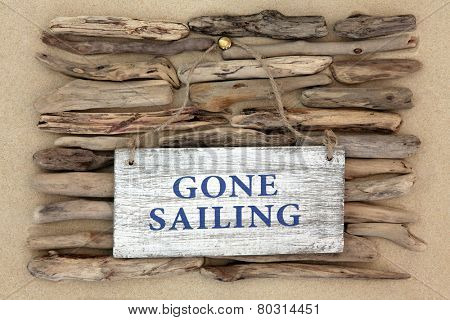 Gone sailing old weathered sign on driftwood and beach sand background.