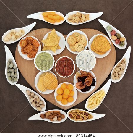 Savoury snack and dip party food selection in porcelain dishes  on a heart shaped wooden board.