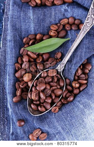 Green petal near the spoon of coffee beans on blue jeans material