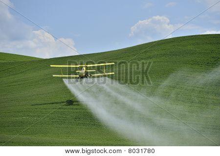 Plumero de cultivo biplano rociar un campo de la granja.