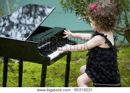 Little Girl Playing On Toy Piano