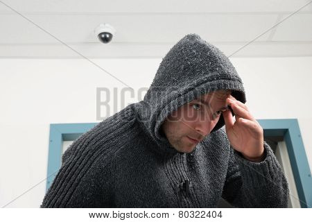 Man In Hooded Sweatshirt With Cctv Camera Behind
