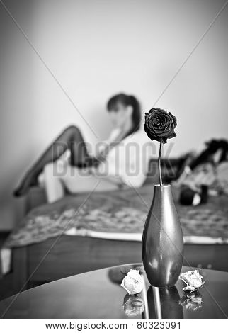 Mysterious brunette putting her stocking with flowers and vase foreground. Sensual woman dressing up