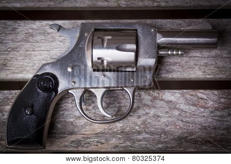 MARYLAND, USA - CIRCA DEC 2014: A staged close-up of an H & R .32 caliber pistol on a gray wooden table, shallow depth of field.